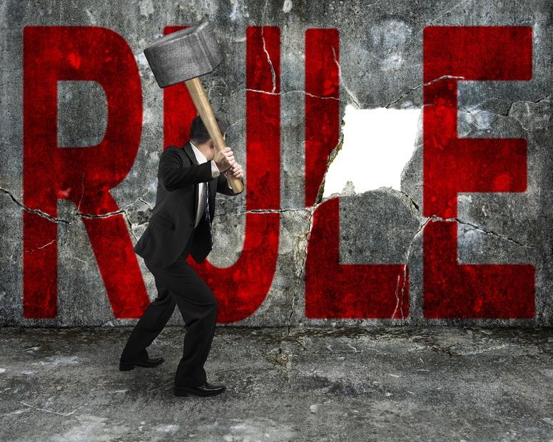 Businessman_holding_sledge_hammer_hitting_rude_rule_word.jpg