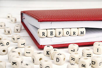 [Image] Red Ruled Book with Boggle Letters Spelling 'Reform' | State Audit Requirements Can Change Significantly Over Time