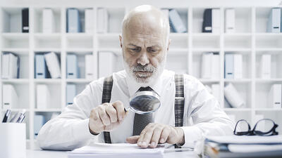 [Image] Older Man Examining Paperwork with Magnifying Glass | Audit Requirements for Nonprofit Charitable Solicitation Registration and Charitable Solicitation Renewal