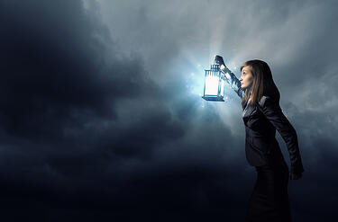 [Image] Woman peering into the mist with a lantern. | Intellectual property due diligence involves searching U.S. patents and trademarks on the USPTO website.